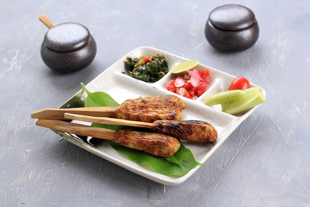 Вкусные традиционные индонезийские балийские кулинарные, сатэ-лилит, сатай из фарша из морепродуктов, приготовленный из тунца и других пряных ингредиентов. в сопровождении самбала матаха,
