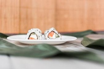 Delicious traditional sushi on plate over table