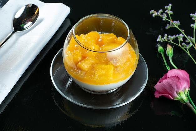 안경에 맛있는 사소한 디저트. 휘핑 크림, 과일, 망고 디저트. 점심 식사 후 과자.