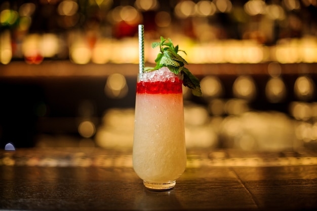 Delicious trinidad swizzle cocktail in the glass with tubule and mint leaves standing on the bar counter