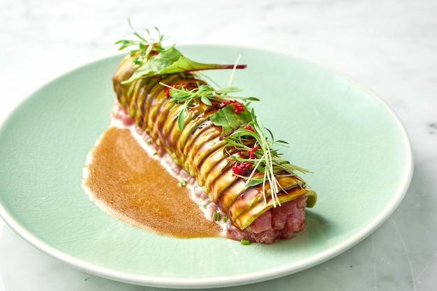 アボカド、コリアンダーを添えた美味しいマグロのタルタルを、ポーチドエッグを添えた白いプレートのライ麦クルトンに添えて。日本料理のおやつ