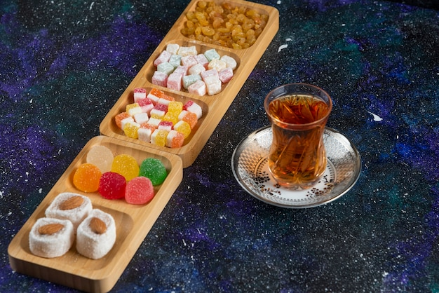 Delicious turkish delights with tea on colorful surface