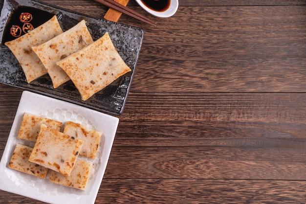 おいしい大根餅、新年の料理のための醤油とレストランでの中国の伝統的な大根ケーキ、クローズアップ、コピースペース、上面図、フラットレイ。