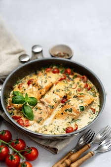 Delicious tuscan cream salmon with spinach in a black pan