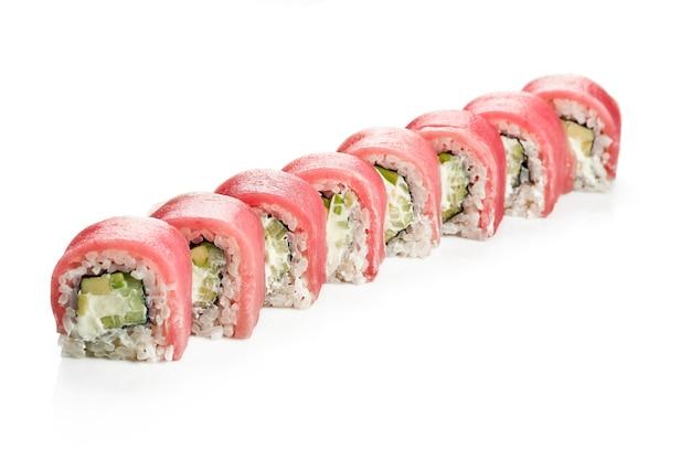 マグロ、キュウリ、アボカドを添えたおいしい裏巻き寿司フィラデルフィア。クラシックな日本料理。食品デリバリー。白で隔離。