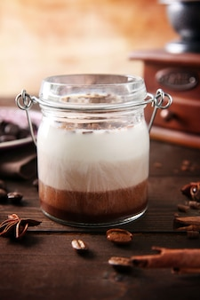 Delicious vanilla-chocolate mousse on wooden table, close up