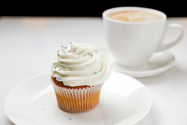 A delicious vanilla cupcake with cream and a cup of cappuccino coffee