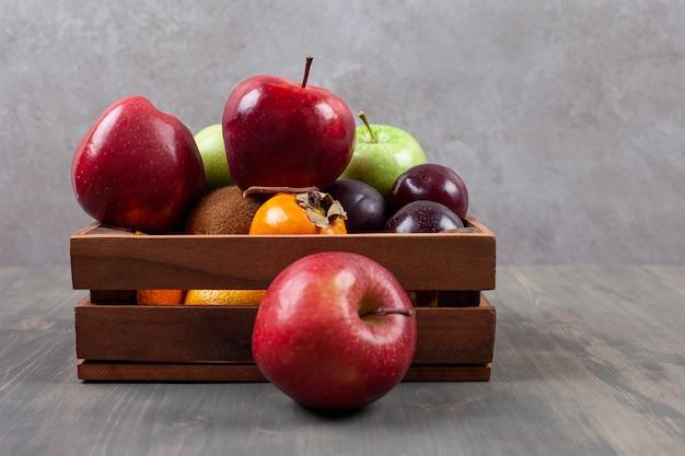 Deliziosi frutti vari su un cesto di legno. foto di alta qualità