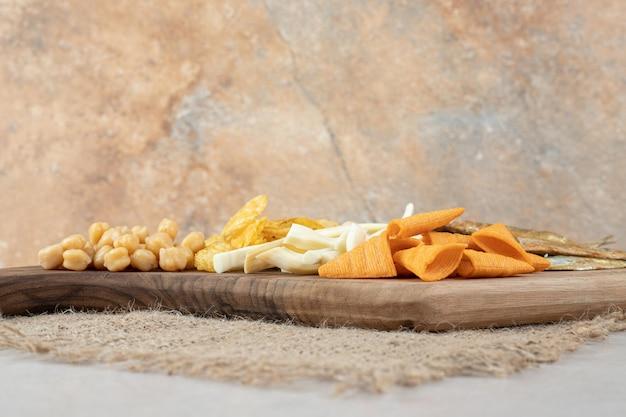 Deliziosi snack vari su tavola di legno