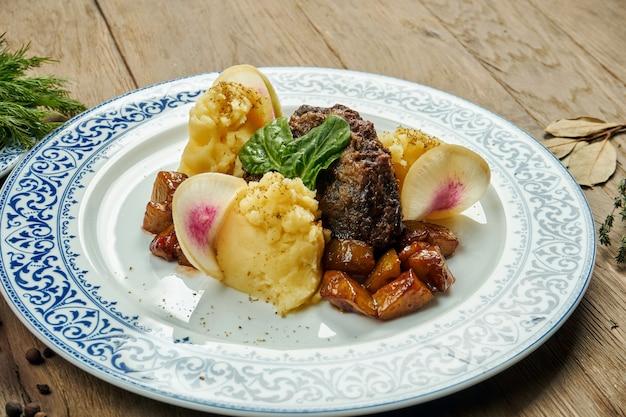 Вкусные телячьи (говяжьи) щеки с медовым соусом и картофельным пюре гарнируют в синюю тарелку на деревянной поверхности. крупным планом вид