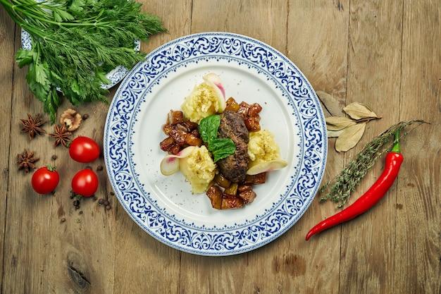 Вкусные телячьи (говяжьи) щеки с медовым соусом и картофельным пюре гарнируют в синюю тарелку на деревянном столе. крупным планом вид