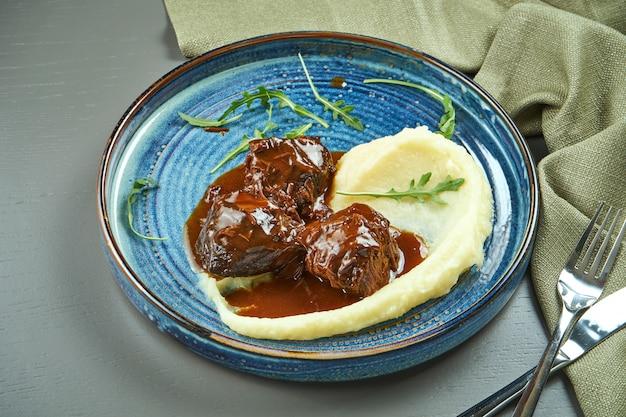 Вкусные телячьи щечки с медовым соусом и пюре гарнир в синюю тарелку на деревянном столе. крупным планом вид
