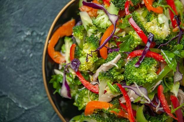 Deliziosa insalata vegana in un piatto con varie verdure fresche su sfondo scuro