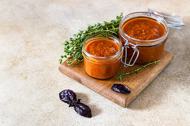 Delicious vegetable caviar in jars, thyme and purple basi