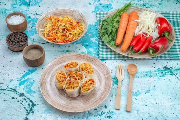 Deliziosi involtini di verdure affettati insieme a insalata fresca e verdure su un pavimento blu brillante