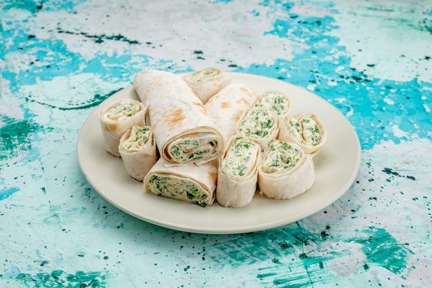 おいしい野菜ロールを丸ごと、明るい青色のフードミールロール野菜スナックでスライス