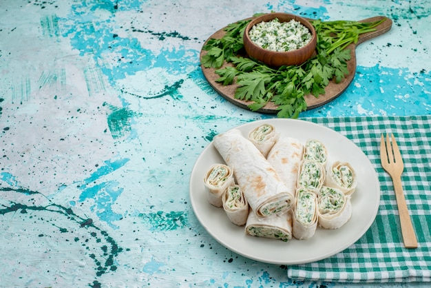 おいしい野菜ロールを丸ごと、グリーンとサラダでスライスした明るい青のフードミールロール野菜スナック