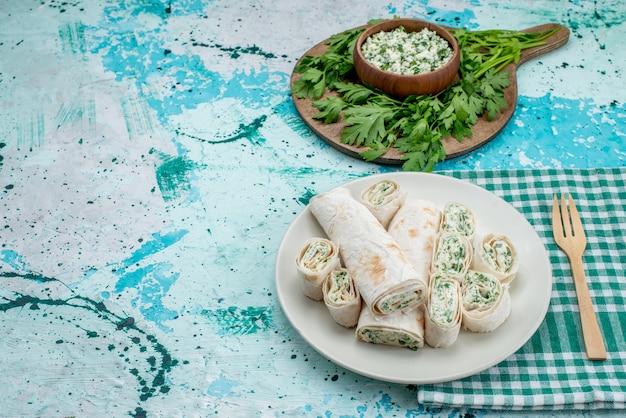 Deliziosi involtini di verdure intere e affettate con verdure e insalata su uno spuntino di verdure blu brillante