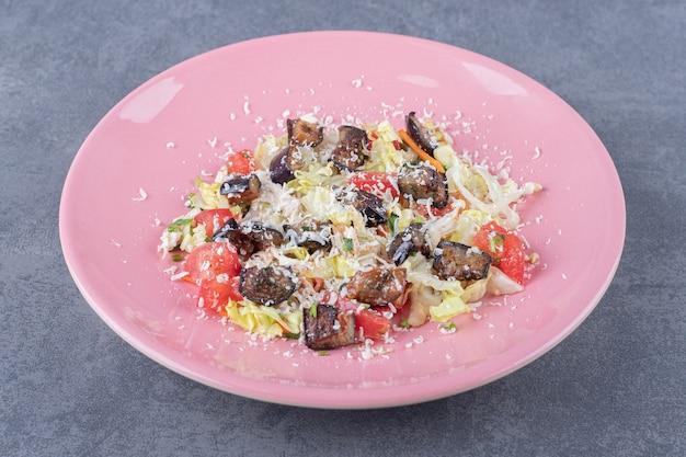 Вкусный овощной салат на розовой тарелке.
