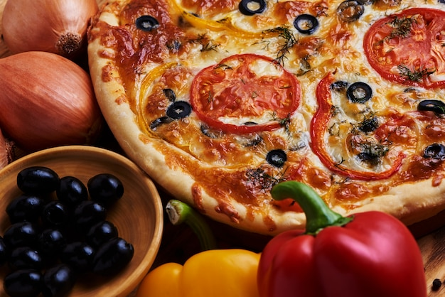 Delicious vegetarian pizza with olives, red pepper and tomato.