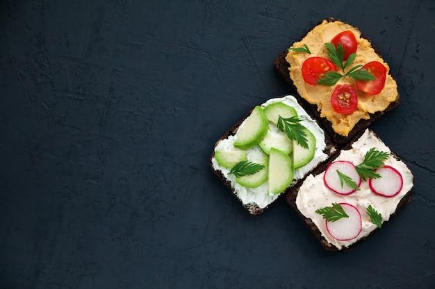 Вкусные вегетарианские тосты из ржаного хлеба с творогом, хумусом, авокадо, редисом и помидорами на черном фоне, копировальное пространство, вид сверху