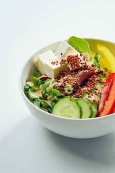 Вкусная овощная миска с огурцом, болгарским перцем, миксом салатов, киноа и тофу в белой тарелке. изолированные на серой поверхности.