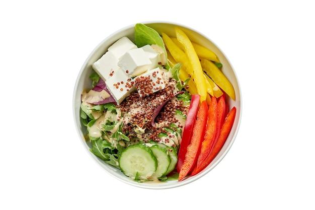 Вкусная овощная миска с огурцом, болгарским перцем, миксом салатов, киноа и тофу в белой тарелке. изолированный на белой поверхности. вид сверху