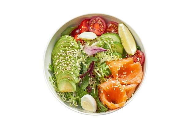 Вкусная овощная миска с лососем, авокадо, огурцом, помидорами черри и микс салатом в белой тарелке. изолированный на белой поверхности. вид сверху