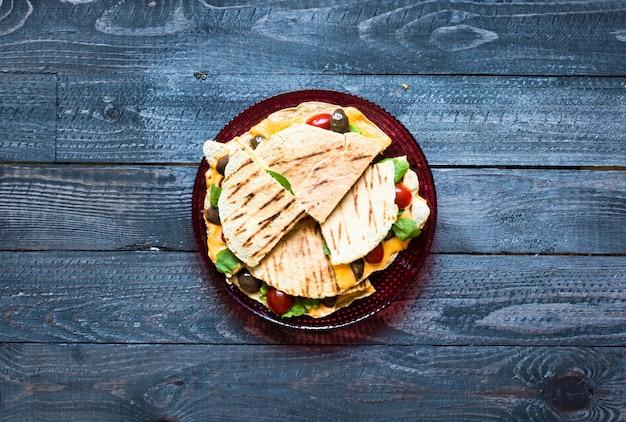 トマト、オリーブ、サラダ、チェダーチーズのおいしい野菜ケサディーヤ