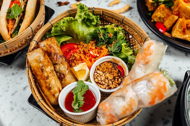 Delizioso cibo vietnamita tra cui pho ga, noodles, involtini primavera sul muro bianco