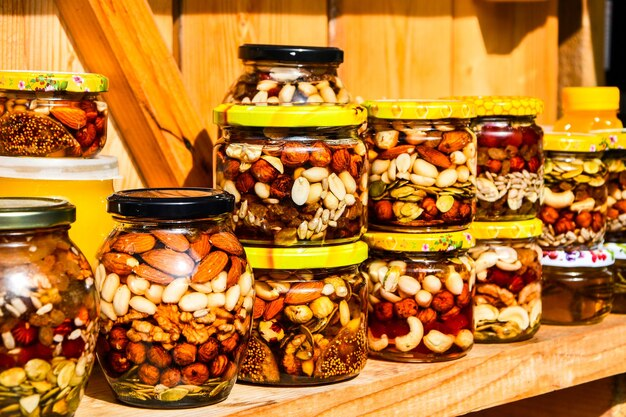 The delicious vitamins are filled with natural honey and cans on the shelves. walnuts and peanuts in a jar filled with honey syrup. counter of honey with nuts