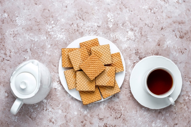 Delicious wafers and a cup of coffee for breakfast on light background, top view