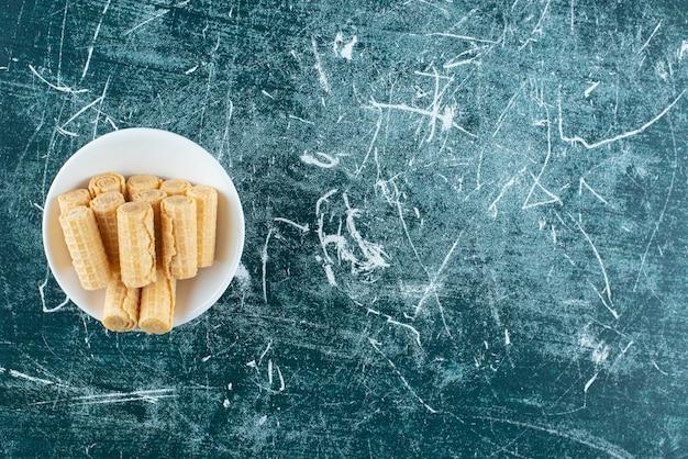 Вкусные вафельные трубочки в белой миске.