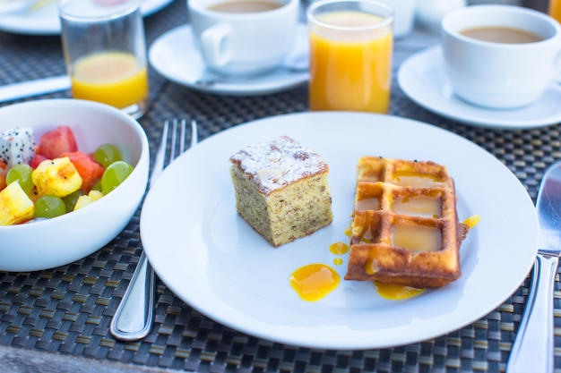 Delicious waffles, cake, coffee and juice served for breakfast at resort restaurant