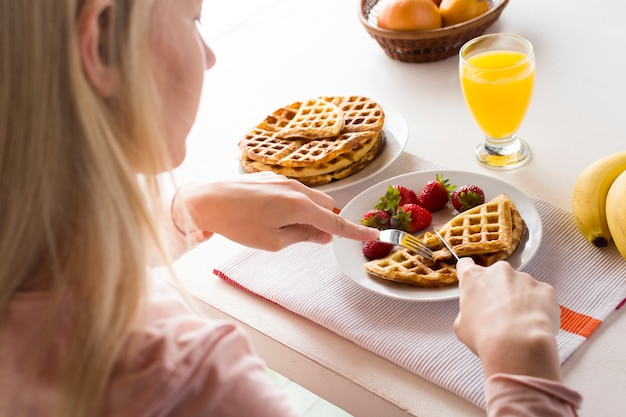 Delicious waffles with strawberries and juice