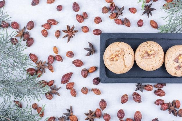 Deliziosi biscotti alla noce sulla piastra scura con cinorrodi