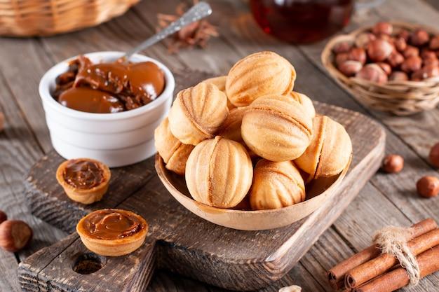 달콤한 연유와 오래 된 나무 테이블에 견과류 가득 맛있는 호두 모양의 쿠키, 근접