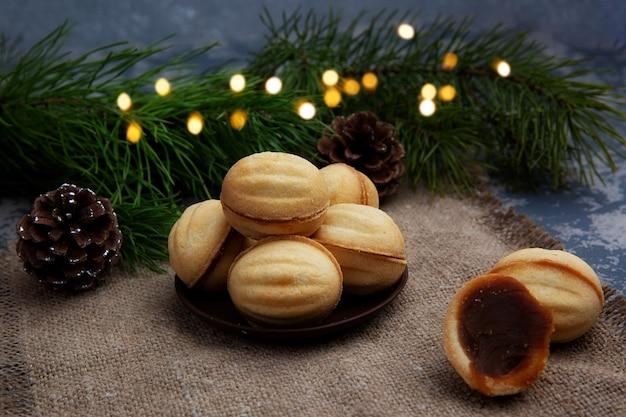 달콤한 연유와 다진 견과류로 가득한 맛있는 호두 모양의 쇼트 브레드 샌드위치 쿠키
