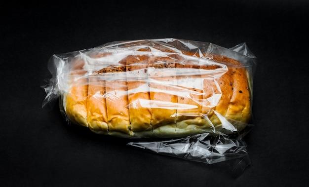 暗いテクスチャ背景のポリ袋の中のおいしい小麦パン