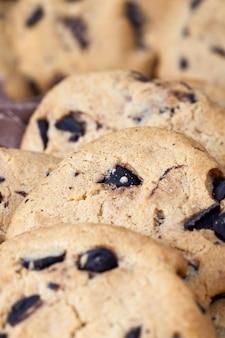 準備されたショートブレッド生地の中においしい小麦粉クッキーとチョコレートドロップ、一緒に折りたたまれた不規則な円形または楕円形の自家製クッキー、クローズアップ