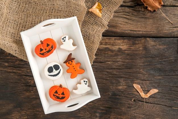 Вкусные белые и оранжевые имбирные печенья в белой деревянной тарелке на коричневой поверхности. пряники на хэллоуин, копией пространства