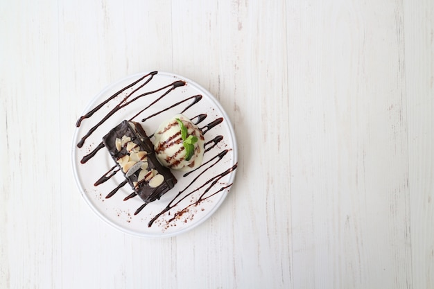 Delicious white and black ice cream on a white wooden table