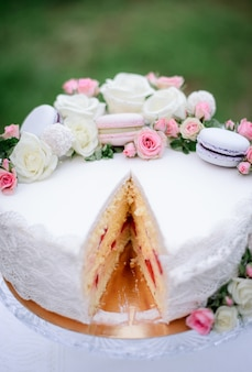 Delicious white cake decorated with pink macaroons and roses