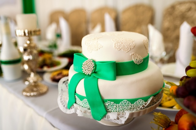 Delicious white cake in the form of a hat with green ribbon and a bow on the table