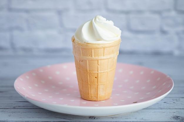 サクサクのワッフルカップに入った美味しい白いクリーミーなアイスクリーム。甘い冷たいデザート。