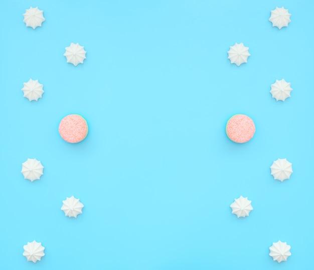 Вкусные белые меренги с одним макарон среди них на синем фоне