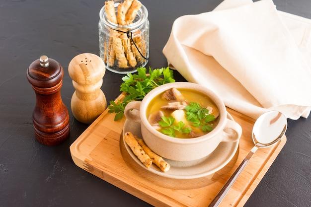 Вкусный суп из белых грибов в суповой тарелке с петрушкой и хлебными палочками. здоровая пища.