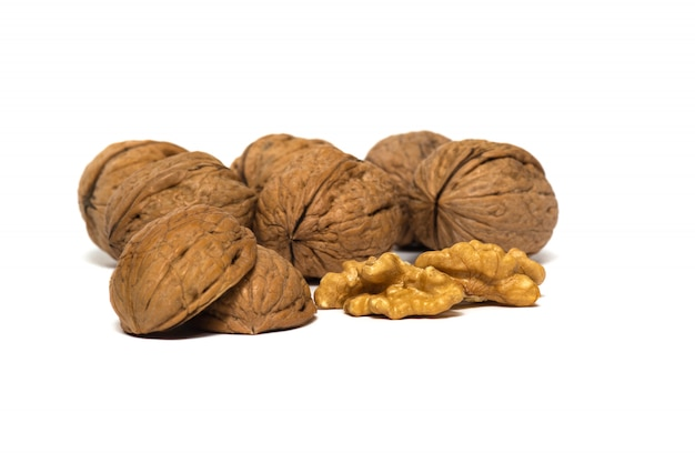 Delicious whole and broken walnuts, isolated on white background