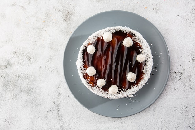 Delicious whole chocolate cake on plate with coconut candies on top on table on marble background. wallpaper for pastry cafe or cafe menu. horizontal.