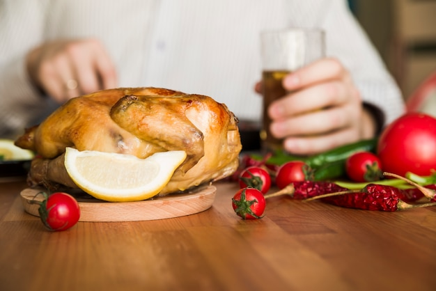 Delicious whole grilled chicken in front of a man holding glass of a beer